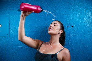 Woman pouring water from water bottle onto her face